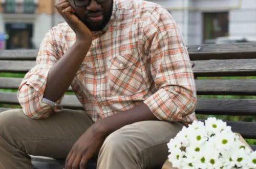 frustrated-afro-american-man-sitting heartbroken with flowers - Opinionatedmaleblog