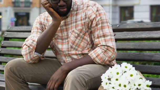 frustrated-afro-american-man-sitting heartbroken with flowers - Opinionatedmaleblog