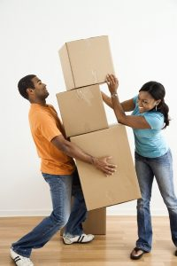 African American female placing boxes on large stack man is holding. - OpinionatedMale.com