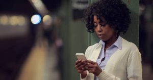 African American Woman on smartphone waiting - OpinionatedMale.com